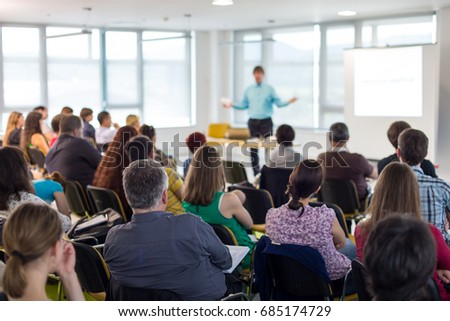 Business and entrepreneurship symposium. Speaker giving a talk at business meeting. Audience in conference hall. Rear view of unrecognized participant in audience. #685174729