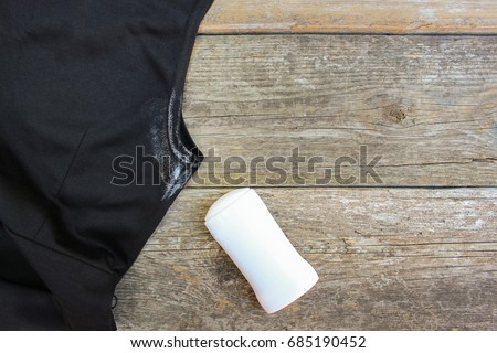 White spot on the dress armpit and deodorant on a wooden background. Top view.  #685190452