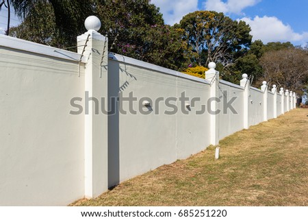 Boundary Wall Electrified Fence Boundary eight foot wall with electrified fence structure. Royalty-Free Stock Photo #685251220