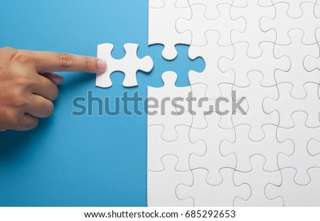 Hand holding piece of white puzzle on blue background. Business and team work concept.  Royalty-Free Stock Photo #685292653