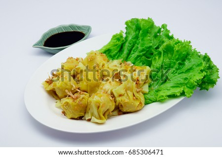 Pork Dumplings (dim sum) with sauce in white plate on white plate and white background #685306471