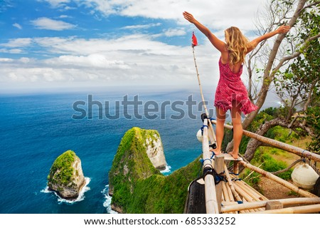 Family vacation lifestyle. Happy woman with raised in air hand stand at viewpoint. Look at Kelingking beach under high cliff. Travel destination in Bali. Popular place to visit on Nusa Penida island. #685333252