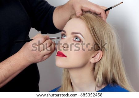 Girl with grey eyes and red lips getting makeup on adorable face by visagiste. Woman with young skin and long blond hair on white background. Visage, cosmetics, skincare, make up. Beauty, youth #685352458