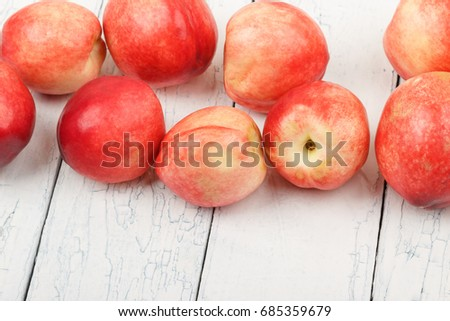 Ripe red peaches on the white wooden table, soft focus background #685359679