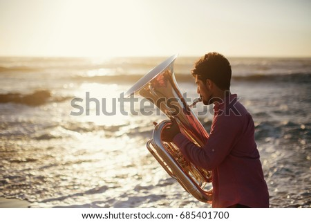 Young man with Tuba musical instrument  on sea shore  outdoor #685401700