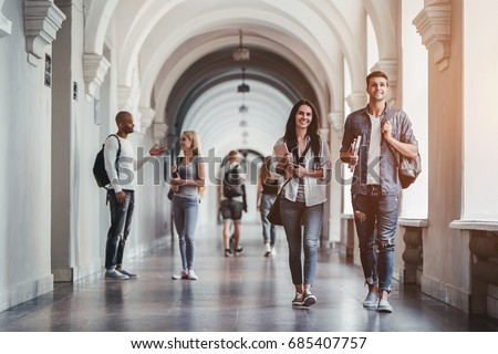 Multiracial students are walking in university hall during break and communicating. Royalty-Free Stock Photo #685407757