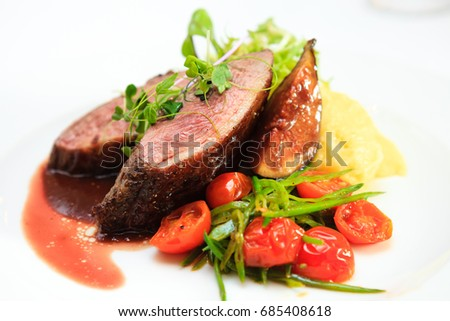 Glazed duck fillet, mashed potatoes seasoned with truffle oil, fig and aniseed sauce #685408618
