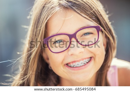 Happy smiling girl with dental braces and glasses.  #685495084