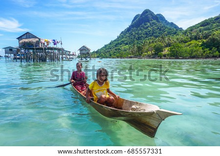 Semporna,Sabah,Malaysia-Apr 23,2017:Sea Gypsy kids on unique handmade boats surrounded by beautiful clear water of the Bodgaya island,Semporna,Sabah,Malaysia. #685557331