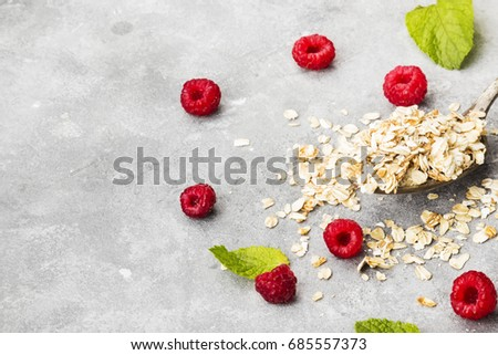 Glanola in spoon with raspberry and mint on a gray background. Copy space. Food background #685557373