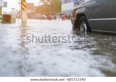 flood water - people walking in the rain on flooded road #685711540