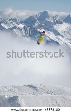 Snowboarder jumping high in the mountains #68578180