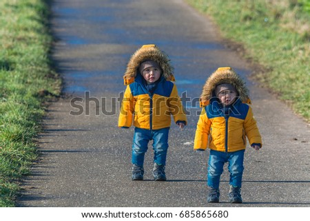 Two small children, twins walking on a country road and looking amazed at the camera. #685865680