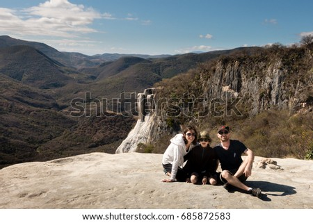 HIERVE EL AGUA, OAXACA, MEXICO - JANUARY 25, 2015: MOTHER, SON AND FATHER POSE FOR PHOTO AT Hierve el Agua, a set of natural rock formations that resemble cascades of water.  #685872583