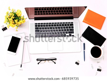 Workspace and laptop keyboard, mobile phone, coffee, glasses and yellow flowers on the white background. Flat lay, top view #685939735