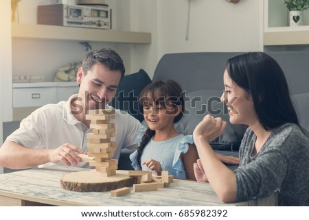 happy family and Daughter playing the wooden blocks tower at home. #685982392