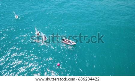 Haifa, Israel - 29 Jul. 2017: Fleet of small sailboats sailing at sea - aerial shot #686234422