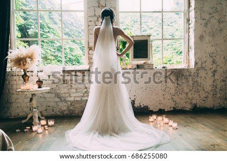 Kind of bride from the back, romantic atmosphere of the bride's morning. The bride in a white wedding dress looks out the window. Royalty-Free Stock Photo #686255080