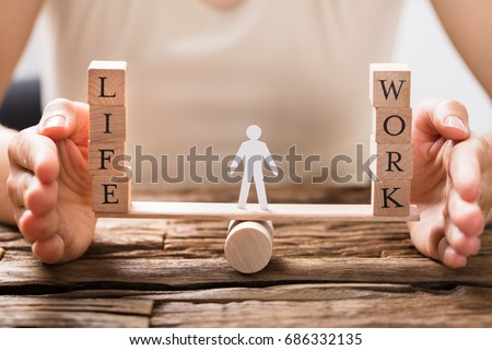 Close-up Of A Human Hand Protecting Balance Between Life And Work On Seesaw Royalty-Free Stock Photo #686332135