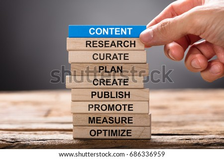 Closeup of hand building content concept with wooden blocks on wood