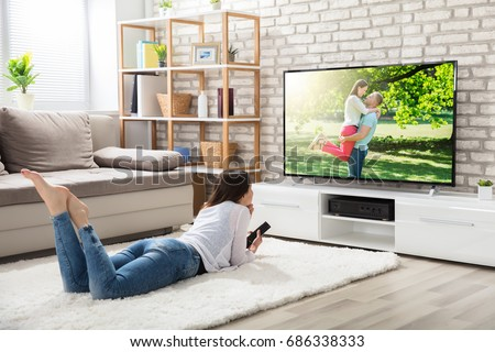 Young Woman Lying On White Carpet Holding Remote Control Enjoying Watching Television At Home Royalty-Free Stock Photo #686338333