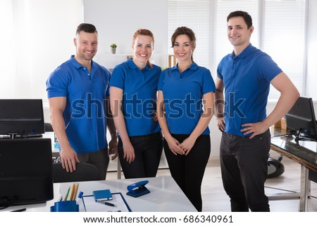 Portrait Of A Smiling Janitors In Uniform At Office Royalty-Free Stock Photo #686340961