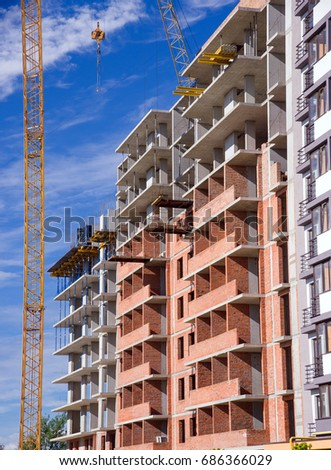 modern apartment building with tower crane on blue sky background #686366029