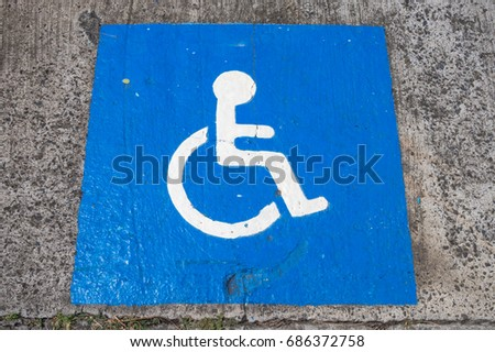 Disabled blue parking sign painted on dark asphalt in Canada #686372758