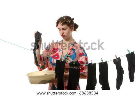 Young tired housewife hangs up socks on  the clothesline #68638534
