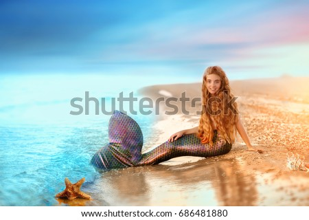 Sea mermaid. Blonde beautiful Siren Mermaid . Mermaid girl with pink tail put feet in water. Top view. Fun, vacation concept. #686481880
