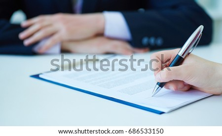 Hands of business woman signing the contract document with pen on desk. selective focus image on sign a contract. #686533150