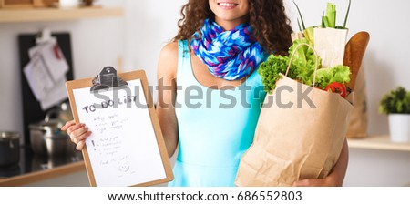 Young woman holding grocery shopping bag with vegetables Standing in the kitchen #686552803