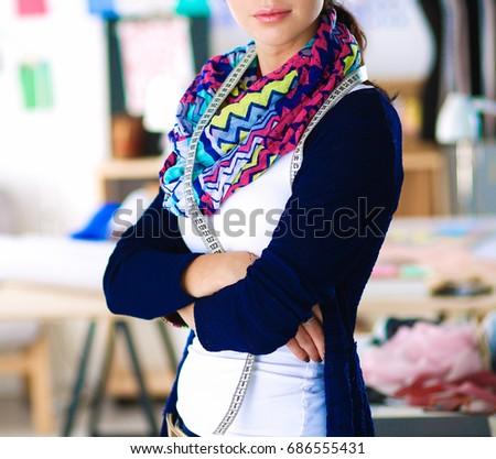 Beautiful fashion designer standing in studio #686555431