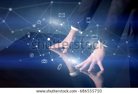 Male hands touching interactive table with blue mixed communication icons in the background #686555710