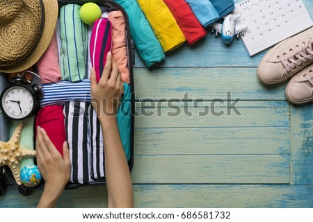 woman packing a luggage for a new journey and travel for a long weekend Royalty-Free Stock Photo #686581732
