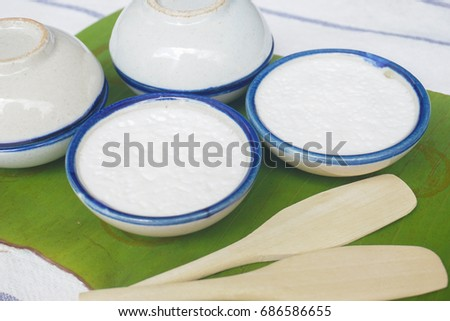 Fresh Homemade Thai Steamed Pandan and Coconut Pudding (Kanom Tuay) in Traditional Thai Ceramic Ramekin serving on a Banana Leaf and Mini Wooden Spatulas #686586655