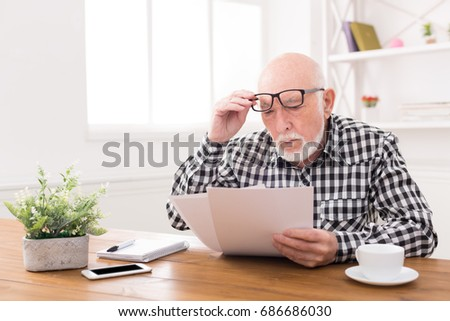 Shocked senior man looking at bills in disbelief, holding his glasses on forehead, copy space #686686030