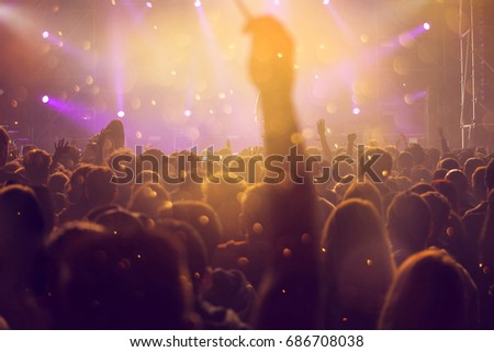 Crowd at concert - Cheering crowd in front of bright colorful stage lights #686708038