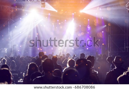 Crowd at concert - Cheering crowd in front of bright colorful stage lights #686708086