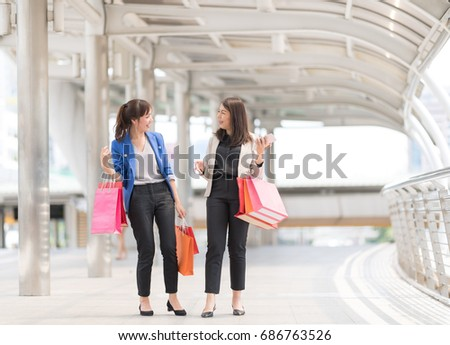 Two Beautiful women with a lot of shopping bags walking back home.Lover Activity Happiness Lifestyle.Friendship Leisure Casual Commercial Shopping Purchase Concept. #686763526