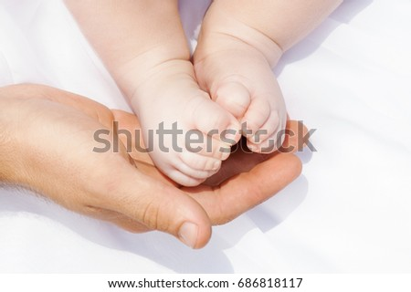 The legs of the child on the father's hands. Little Newborn Baby's feet on male Shaped hands on the white background.Sensual conceptual image of fatherhood. Concept of happy family #686818117