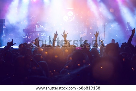 Photo of many people enjoying concert, crowd with raised up hands dancing in nightclub, audience applauding to musician band, night entertainment, music festival. #686819158