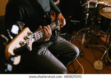 Guitarist playing bass guitar in studio closeup. Music band recording process, live rock concert #686829241