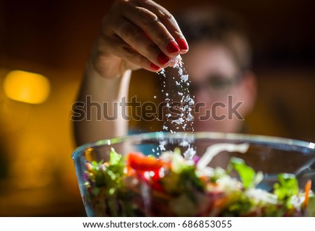 Woman preparing healthy salad in kitchen, adding salt to the bowl. Royalty-Free Stock Photo #686853055