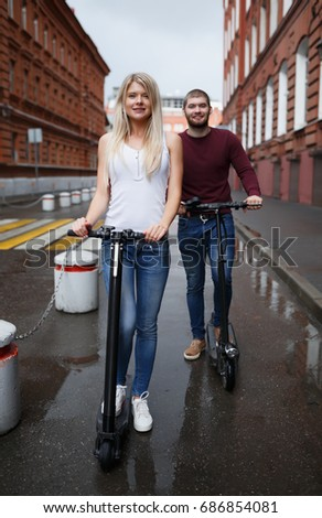 Beautiful girl and cute guy with black electronic kick scooters stand in full growth and look at the camera and smile on the city bridge #686854081
