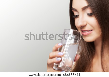 Drink water. Happy young beautiful woman drinking water. A smiling female model holding a transparent glass in his hand. Focus on your hand. On a gray background. #686855611