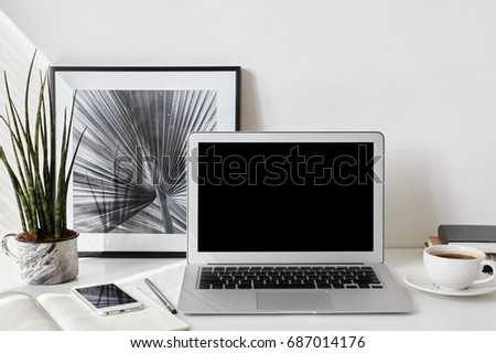 Set of modern electronic devices on white office desk. Freelancer's desktop with blank screen laptop, stationery items, framed picture, mobile phone, decorative plant and cup of coffee. Mock up