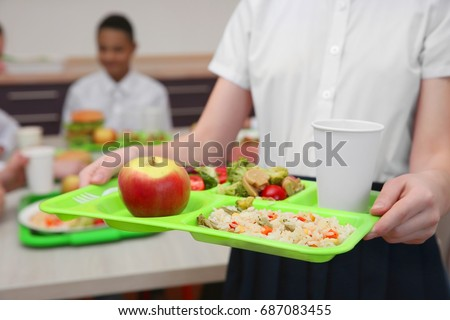 Girl holding tray with delicious food in school canteen, closeup Royalty-Free Stock Photo #687083455