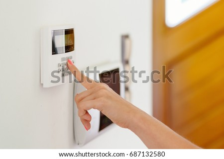 Young woman entering authorization code pin on home alarm keypad. Home security concept #687132580