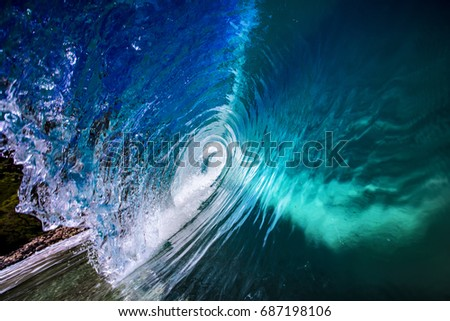 Blue Ocean sea wave inside the barrel. Rip curl surfing wave shape. Sea Water rolling to the shore. Nobody on the picture. Water splashes with drops and reflections.